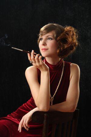 The beautiful girl smokes a thin cigarette