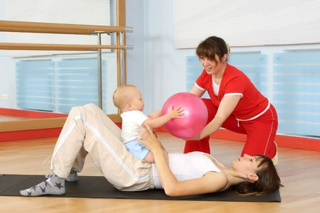 Mother and the child are engaged with the instructor in a sports hall