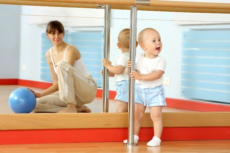 Mother and the child are engaged with the instructor in a sports hall Stock Photo - 5805239