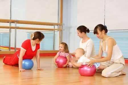 sports hall: Mother and the child are engaged with the instructor in a sports hall