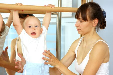 Mother and the child are engaged with the instructor in a sports hall photo