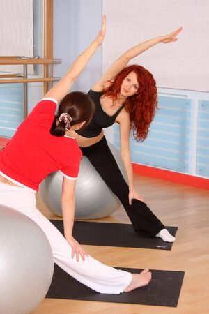 salle de sport: The pregnant woman with the instructor is engaged in gymnastics in a sports hall