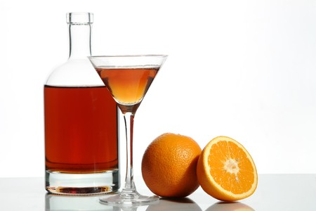 Bottle with an alcoholic drink, a glass and an orange on a white background