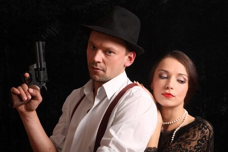 Portrait of the man in a hat with a pistol and the beautiful woman. In style of a retro. Stock Photo