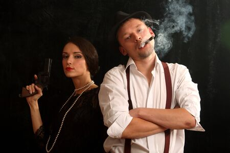 Portrait of the man in a hat with a cigar and a pistol and the beautiful woman. In style of a retro.