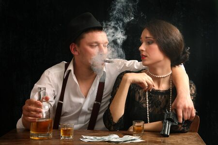 The man-gangster and the beautiful girl talk in a bar photo