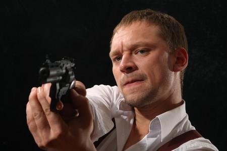 guardaespaldas: La agresiva hombre-g�ngster con una pistola. Un retrato sobre un fondo negro.