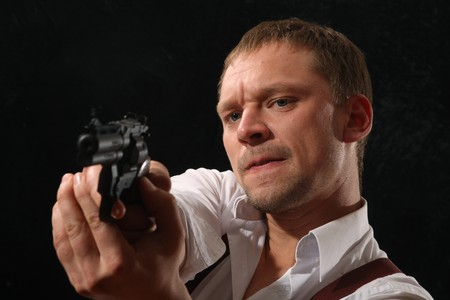 The aggressive man-gangster with a pistol. A portrait on a black background. Stock Photo