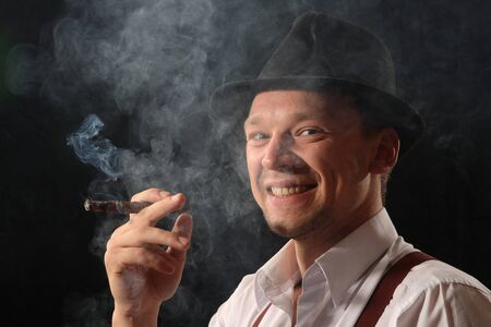 Portrait of the young man against a dark background in the black hat, smoking the big cigar. photo