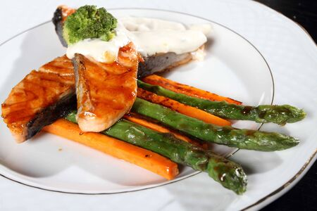 Two big fried thoroughly pieces of a salmon with an asparagus and carrots photo