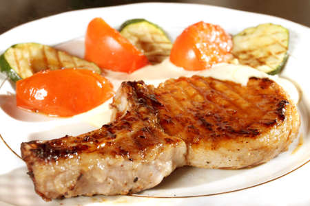 � fond: The big fried thoroughly piece of meat on a plate with tomatoes and avocado