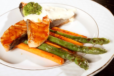 Two big fried thoroughly pieces of a salmon with an asparagus and carrots Stock Photo