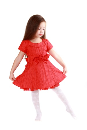 little girl dancing: The little girl in brightly red dress on a white background Stock Photo
