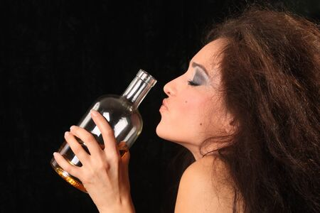 The beautiful girl in a black dress against a dark background with a brandy bottle