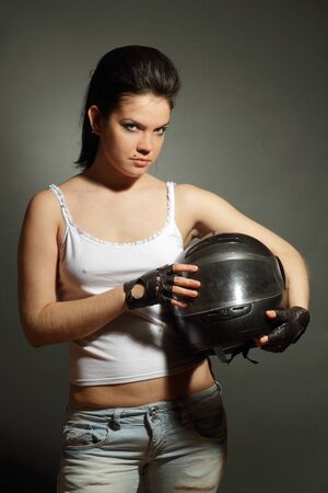 The girl with a motorcycle helmet on a gray background photo