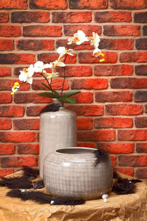 Flowers in a vase on a metal shod table against a wall from a red brick. photo