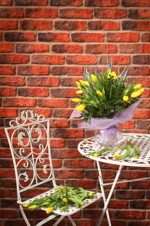 Flowers on a metal shod table against a wall from a red brick?  photo