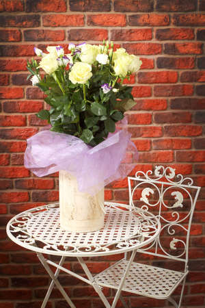 Bunch of flowers on a metal shod table against a wall from a red brick photo