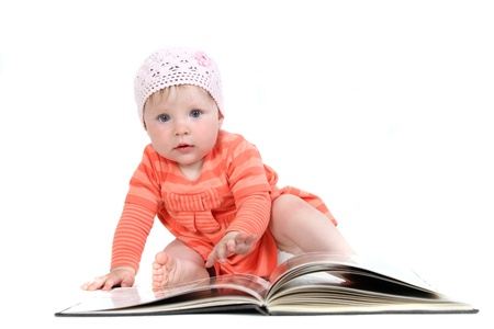 The little blue-eyed girl thumbs through the book. A portrait on a white background. Option 9 Stock Photo