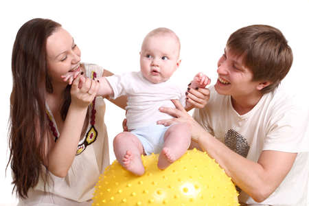 Portrait of a young family on a white background. The father, mum and the kid. A horizontal format. The kid sits on a yellow ball, parents look at the kid Stock Photo - 13074549