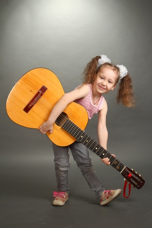 the little girl costs with a big guitar, a look in a lens, a vertical shot, a double 1 photo