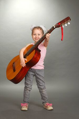 the little girl costs with a big guitar in hands, a look in a lens, smiles, a vertical shot, a double 2 photo