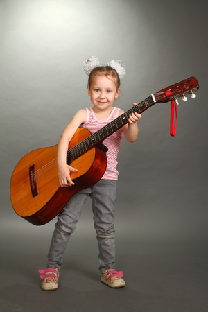 the little girl costs with a big guitar in hands, a look in a lens, smiles, a vertical shot photo