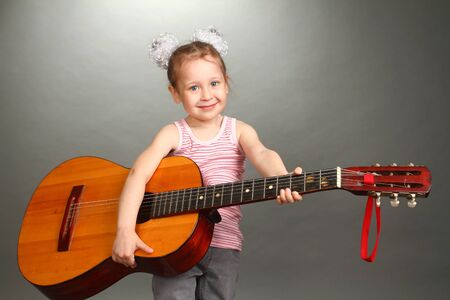 the little girl costs with a big guitar in hands, a look in a lens, smiles, a double 5 photo
