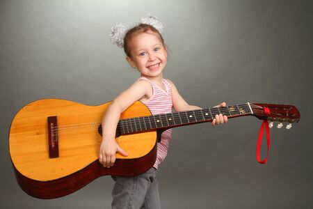 the little girl costs with a big guitar in hands, a look in a lens, smiles, a double 2 photo