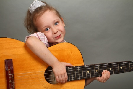 the little girl with a big guitar, a close up, a look in a lens Stock Photo - 13248854