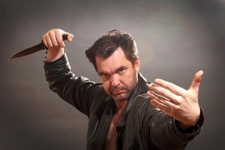 combattimenti: l'uomo tiene il soldato in una giacca di pelle nera in una mano un pugnale con un bordo nero Archivio Fotografico