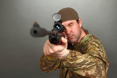 the man in a camouflage aims from a rifle with a riflescope. double 5