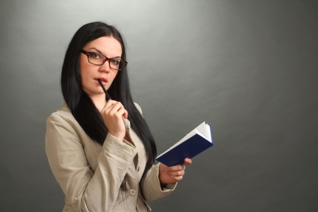 the thoughtful girl, the brunette wearing spectacles with the handle and a notebook on a gray background, looks in the chamber