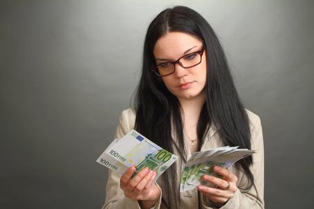 bacon portrait: the girl the brunette wearing spectacles counts money Stock Photo