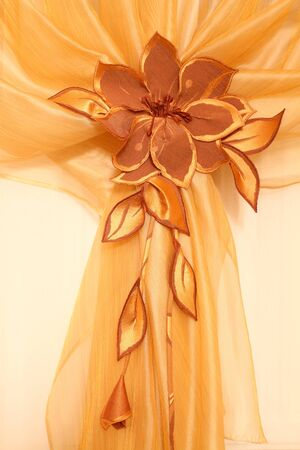 organza: fragment of a window curtain with the embroidered flower from tulle, a vertical shot