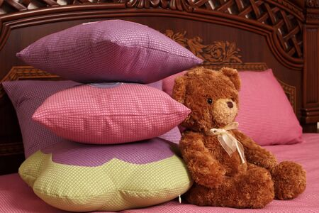 fragment of an interior of a bedroom. some embroidered pillows on a bed and a teddy bear Stock Photo - 13472082
