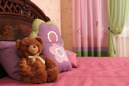 fragment of an interior of a bedroom. some embroidered pillows on a bed and a teddy bear, a double 5 photo