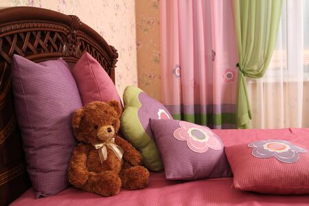 fragment of an interior of a bedroom. some embroidered pillows on a bed and a teddy bear, a double 6 photo