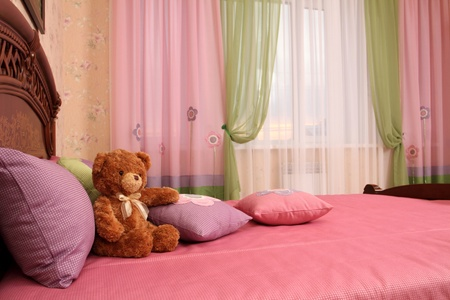 fragment of an interior of a bedroom. some embroidered pillows on a bed and a teddy bear, a double 7