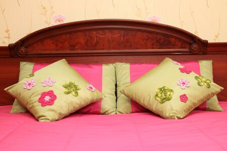 fragment of an interior of a bedroom. a bed headboard with small pillows, a close up photo