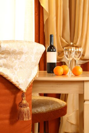 table fragment, on it a bottle of wine and two glasses, in the foreground a chair back Stock Photo - 13472087