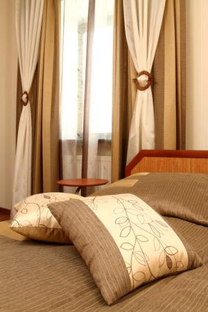 fragment of an interior of a bedroom with a bed and the embroidered pillow Stock Photo - 13472036