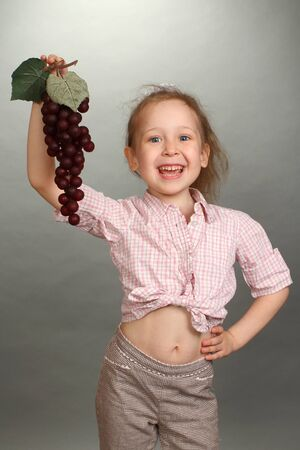 the little girl holds a brush of red grapes in a hand and smiles photo