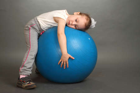 the little girl, the blonde, embraces hands a big dark blue ball Stock Photo - 13472102