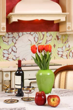 the wine bottle, two glasses, apples and bouquet of tulips in a green vase on a kitchen table photo