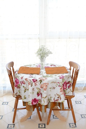 interior of the modern apartment, table with a bunch of flowers, two chairs against a big window, a vertical shot photo
