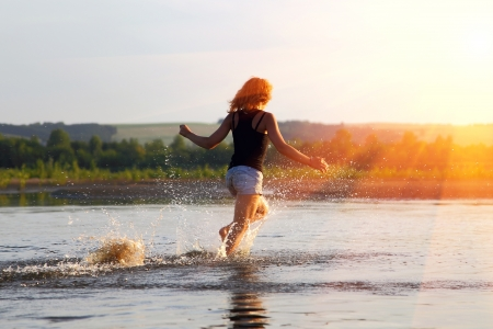 the girl runs on water on a meeting to the coming sun photo