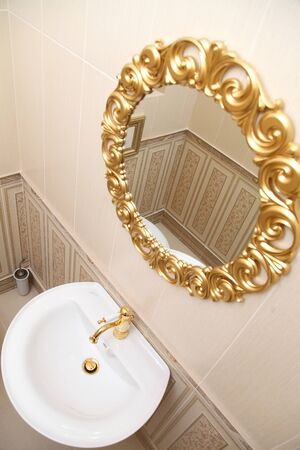 bathroom design: The washing room with a sink and a mirror with a gold pattern