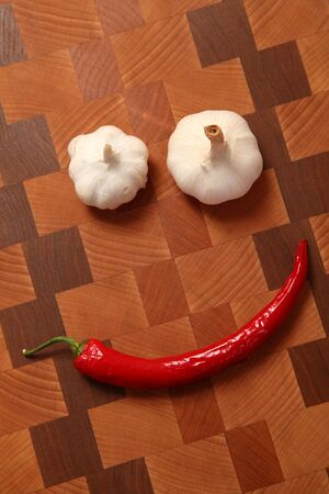 two heads: two heads of garlic and chili pepper on a chopping board Stock Photo