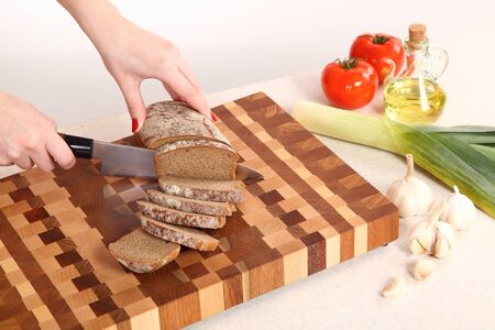 vegetable oil: the bread cut by means of a knife on a chopping board, vegetables and vegetable oil